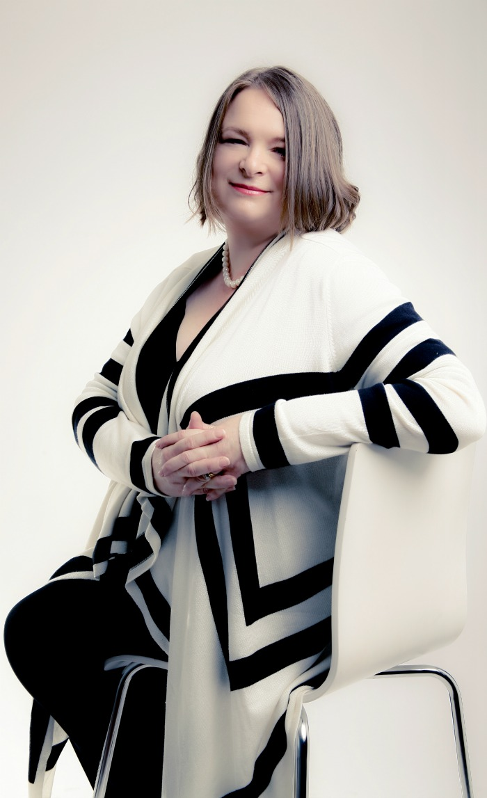 Heather Denny | the Hypnotherapist | www.thehypnotherapist.co.uk - sitting on a chair wearing a black and cream jacket